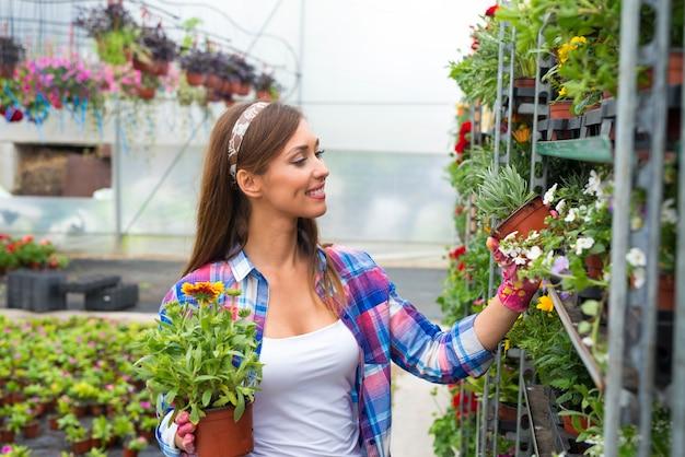 Bloemist die bloemen in tuincentrum schikt