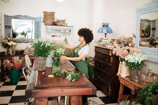 Bloemist die bloemen in winkel schikken