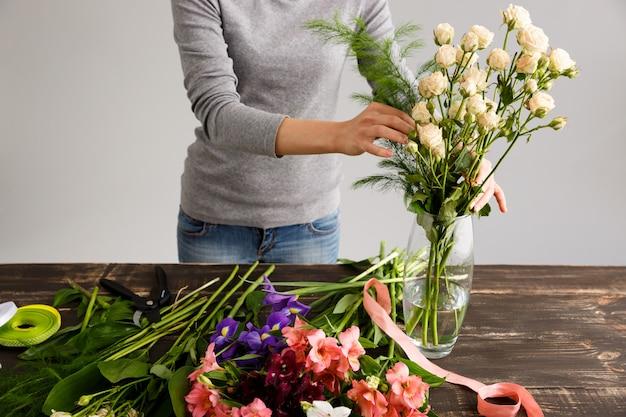 Bloemist die boeketbloemen in vaas maakt