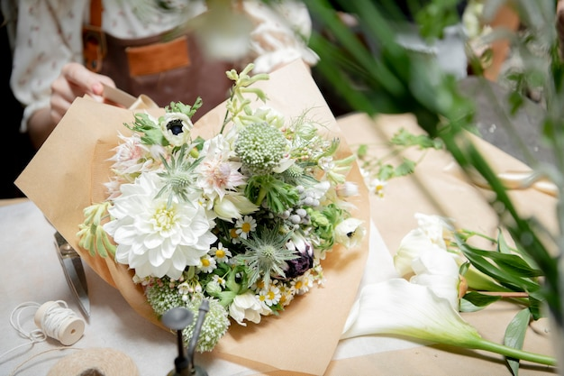 Bloemist die boeketten maakt bij een bloemenwinkel