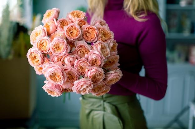 Bloemist die een boeket houdt. prachtige lentebloemen. regeling met bloemenmix.