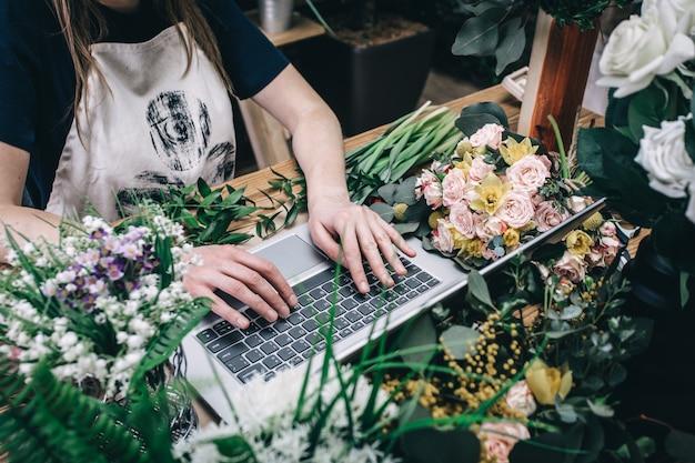 Bloemist die met laptop werkt