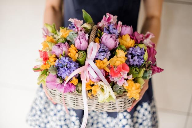 Bloemist die mooie rieten mand met bloemen houdt