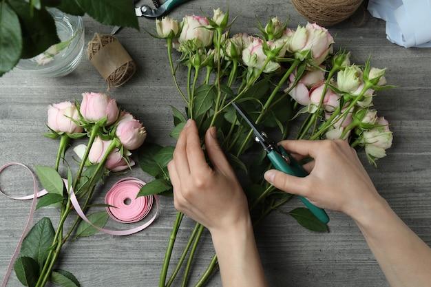 Bloemist die rozenboeket op donkere geweven maakt