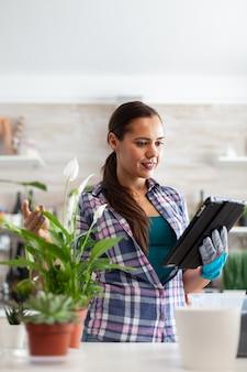 Bloemist die tablet-pc gebruikt voor bloemontwerp in de keuken thuis