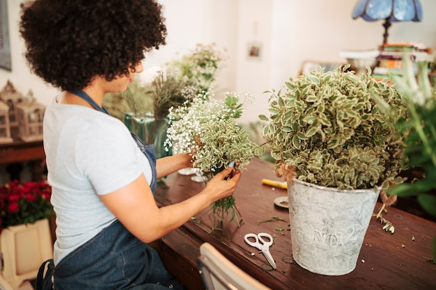 Bloemist die witte bloeminstallaties op houten bureau schikken