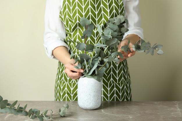 Bloemist houdt eucalyptustakken in vaas op grijze gestructureerde tafel