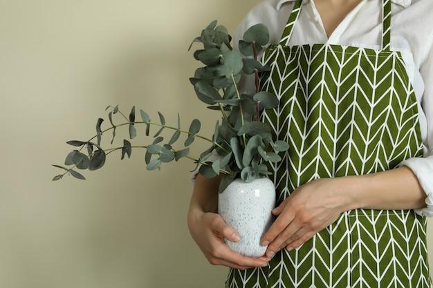 Bloemist houdt vaas met eucalyptus op licht beige achtergrond