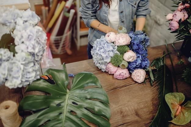 Bloemist in een bloemenwinkel die een boeket maakt