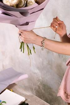 Bloemist inpakboeket van roze bloemen. de decorateur werkt in een kas met een roze boeket. floristiek workshop, vaardigheid, decor, klein bedrijfsconcept