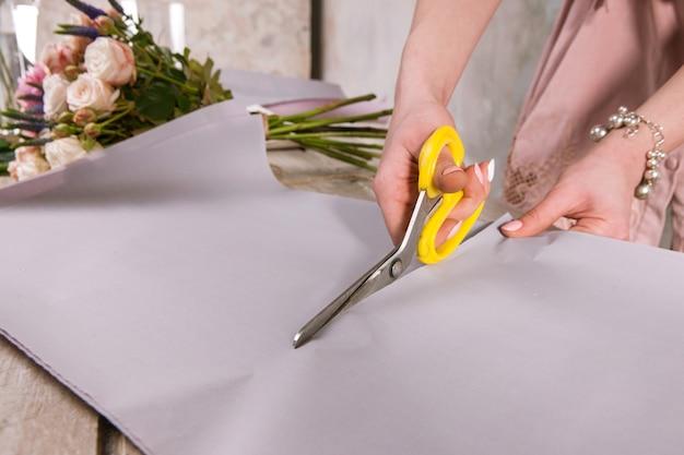 Bloemist inwikkeling boeket van roze bloemen close-up. de decorateur werkt in een kas met een roze boeket. floristiek workshop, vaardigheid, decor, klein bedrijfsconcept
