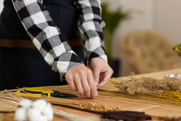 Bloemist maakt droge composities van gedroogde bloemen op houten tafel, close-up shot