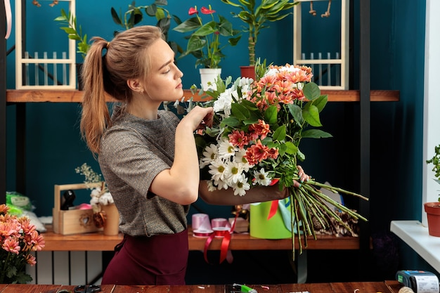 Bloemist maakt een boeket. een jong volwassen meisje houdt een groot boeket veelkleurige chrysanten in haar handen en controleert het.