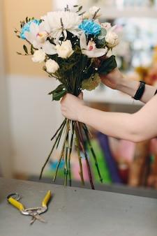 Bloemist maakt een boeket in een bloemenboetiek