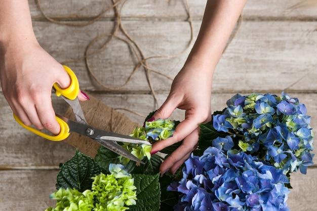 Bloemist maakt een boeket kasbloemen. de decorateur werkt in een kas met een paars boeket. floristiek workshop, vaardigheid, decor, klein bedrijfsconcept