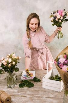 Bloemist maakt een boeket roze bloemen bij bloemisterij. de decorateur werkt in een kas met een roze boeket. floristiek workshop, vaardigheid, decor, klein bedrijfsconcept