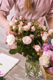 Bloemist maakt een boeket rozenbloemen. de decorateur werkt in een kas met een roze boeket. floristiek workshop, vaardigheid, decor, klein bedrijfsconcept