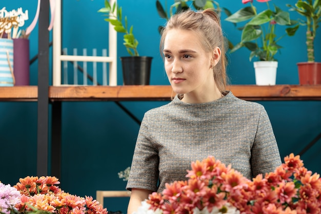 Bloemist maakt een boeket van veelkleurige chrysanten. een jong volwassen meisje kijkt opzij.