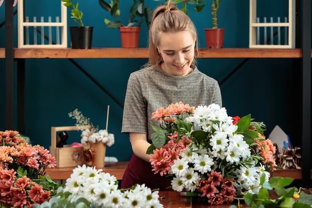 Bloemist maakt een boeket van veelkleurige chrysanten. een jong volwassen meisje werkt met enthousiasme.