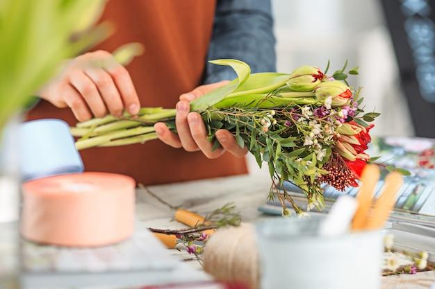Bloemist op het werk: de vrouwelijke handen van een vrouw die een modern boeket van verschillende bloemen maakt