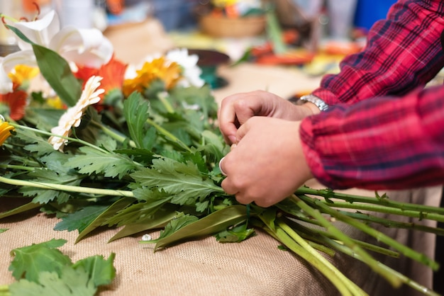 Bloemist op het werk. vrouwenhanden die mooi boeket van bloemen maken.