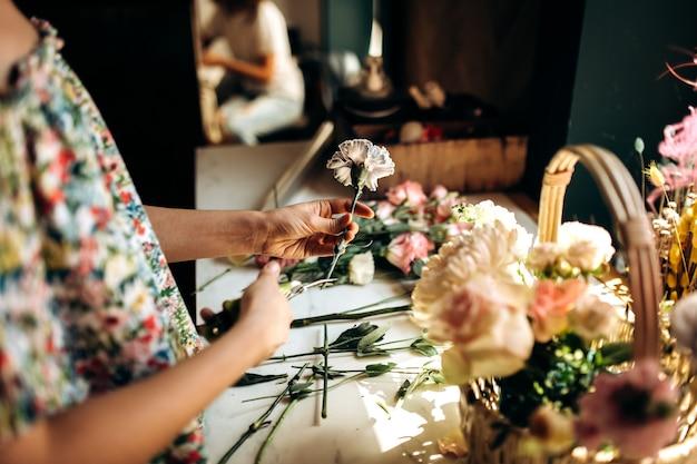 Bloemist snijdt een stengel van een anjer en verzamelt een boeket in de mand van verse bloemen in de bloemenwinkel.