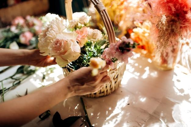 Bloemist verzamelt een boeket in de mand van verse pioenrozen en rozen in de bloemenwinkel.