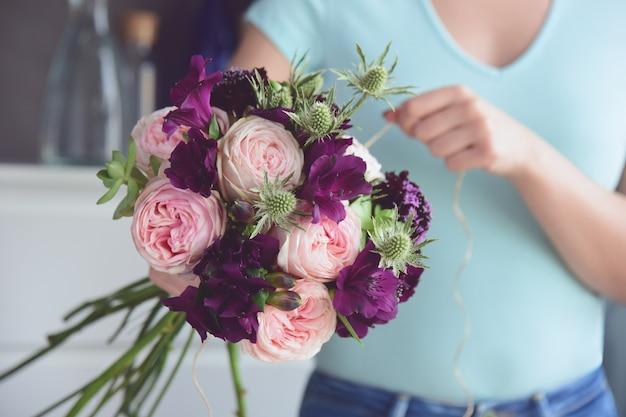 Bloemist voltooit een ongewoon bruidsboeket van pioenrozen, alstromeria, distels en vetplanten