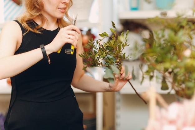 Bloemist vrouw maakt boeket in bloemenboetiek.