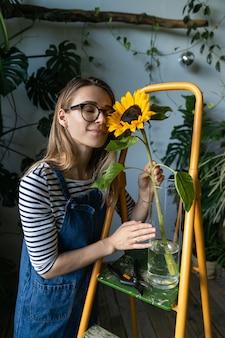 Bloemist vrouw omringd door tropische planten geniet van een prachtige zonnebloem in vaas