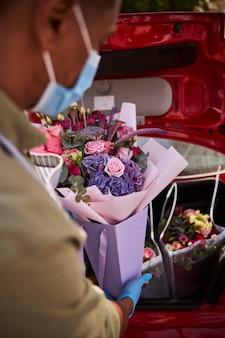 Bloemist winkelmedewerker die voorzichtig een pakje bloemen laat zakken in een achterkoffer van een auto