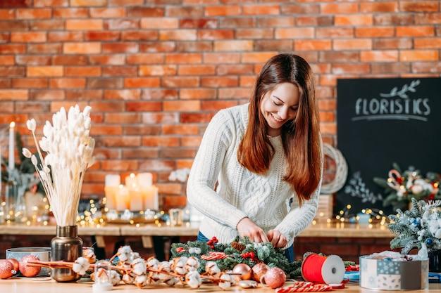 Bloemist workshop. creatieve dame bezig met nieuwe feestelijke winterdecoratie.