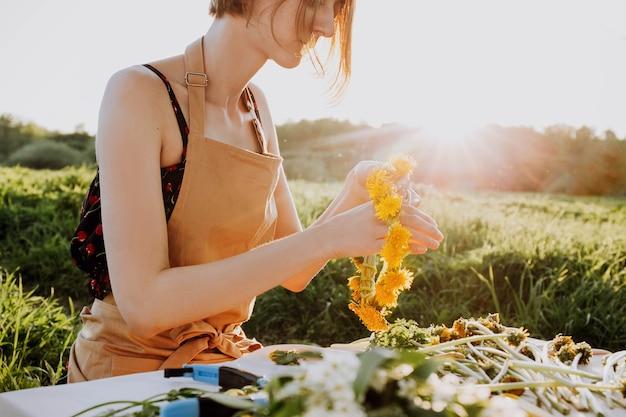 Bloemist workshop. mooie vrouw die krans maakt van paardebloemen. romantische achtergrond van bloemist op het werk.