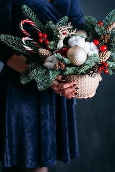 Bloemist workshop. vrouw in blauwe jurk met pot met dennenboom, herten, kerstballen, zuurstokken.