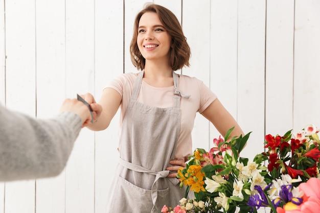 Bloemistdame die zich met bloemen in workshop met koper bevinden.