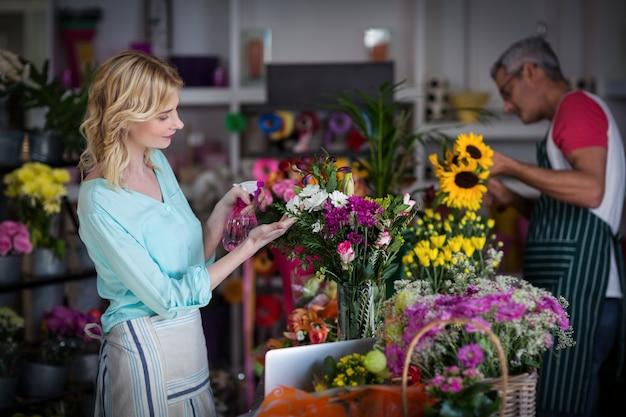 Bloemisten die water bespuiten op bloemen in bloemenwinkel