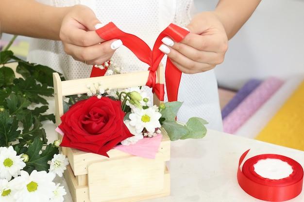 Bloemistenmeisje dat in een bloemenwinkel werkt zachte tinten verse lentebloemen verpakt in decoratief papier of in een doos geplaatst bloemistenzaak