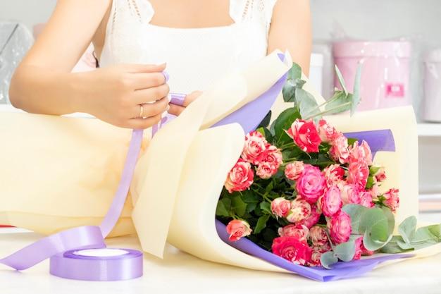 Bloemistenmeisje werkt in een bloemenwinkel zachte tinten verse lentebloemen verpakt in decoratief papier bloemistenzaak