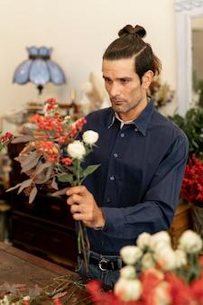 Bloemistmannetje dat wordt geconcentreerd en door bloemen wordt omringd