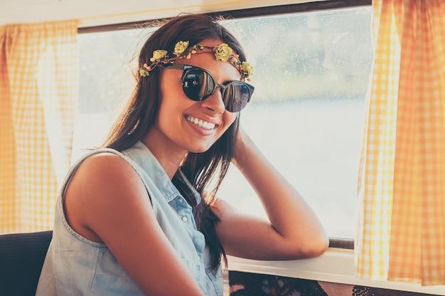 Bloemkind in de zon. gelukkige jonge vrouw die lacht naar de camera terwijl ze in het retro busje zit