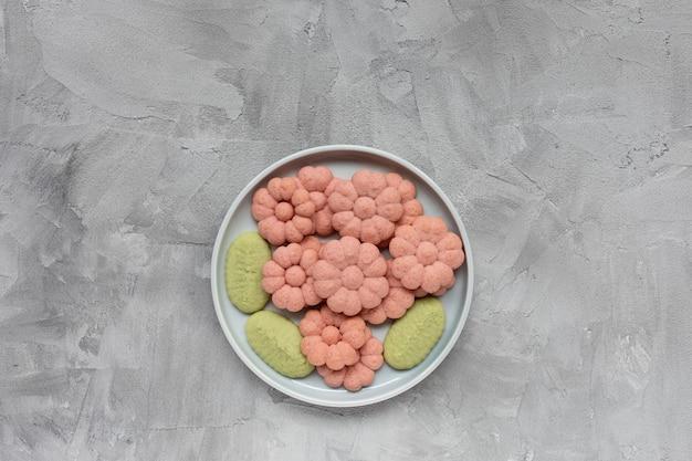 Bloemkoekjes op een plaat op een grijze achtergrond het koken concept van de de lentevakantie