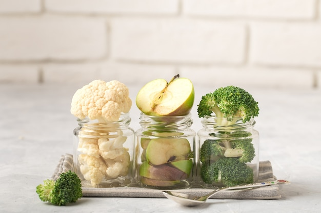 Bloemkool, broccoli, appelschijfjes, in potten voor babyvoeding, op een rij, op een stoffen servet, metalen lepel, lichte achtergrond