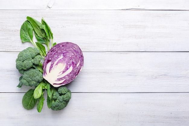 Bloemkool, broccoli en blauwe kool op een witte houten achtergrond. achtergrondmenu eten.