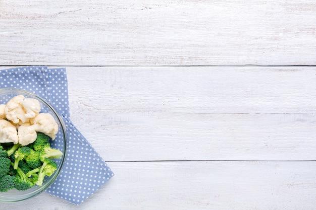 Bloemkool en broccoli in een transparante kom op een witte houten achtergrond. achtergrondmenu eten