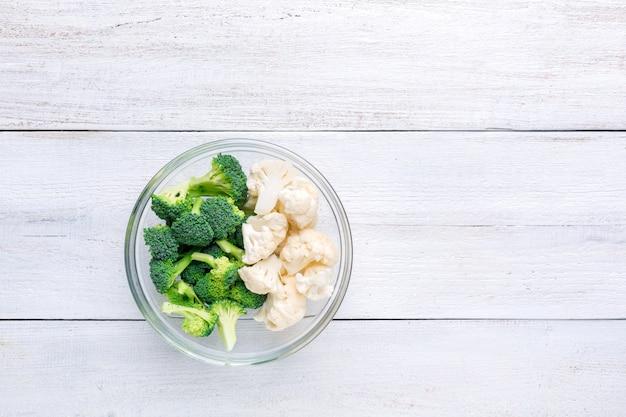 Bloemkool en broccoli in een transparante kom op een witte houten.