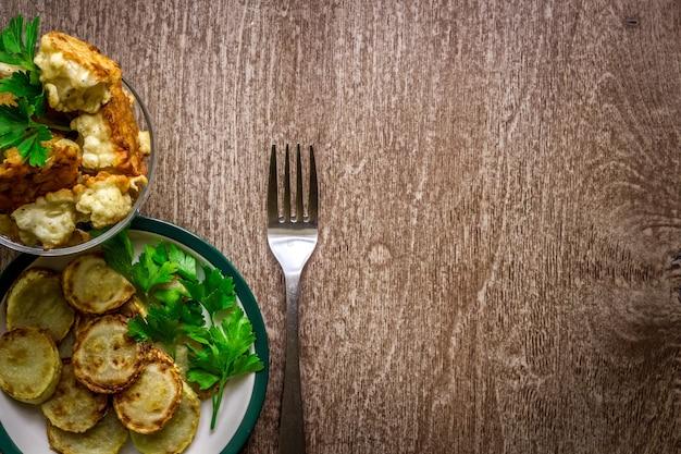 Bloemkool en courgette gebakken in beslag op een houten ondergrond. bovenaanzicht. ruimte kopiëren. stilleven. plat leggen