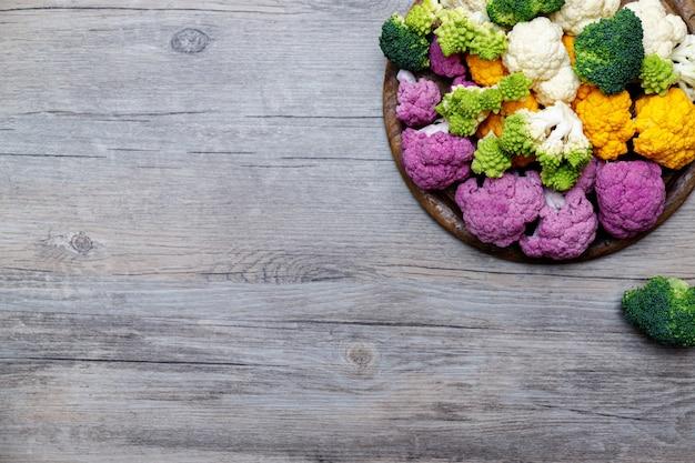 Bloemkool en romanesco-broccoli op houten achtergrond. gezond voedselconcept.