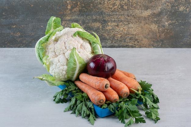 Bloemkool, wortelen en ui op blauw bord. hoge kwaliteit foto