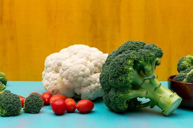 Bloemkoolbroccoli en kersentomaat op blauwe lijst aan gele oppervlakte