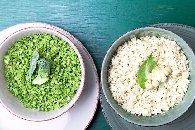 Bloemkoolrijst en broccolirijstkom op groen. bovenaanzicht overhead. copyspace. shredded.